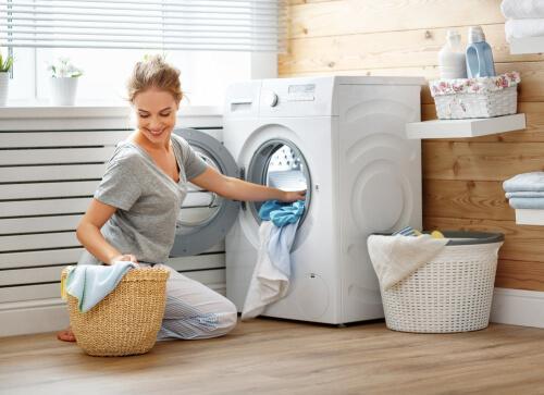 ドラム式洗濯機でに洗濯物を入れている女性