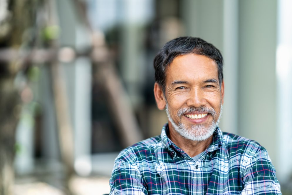Signs of prostate cancer: Man in a plaid shirt smiling
