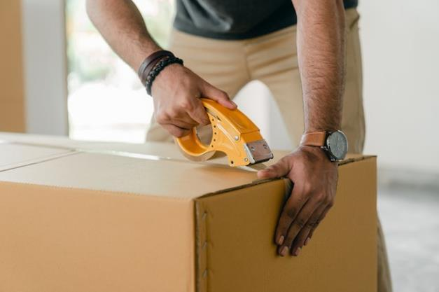 Man sealing a box with tape.