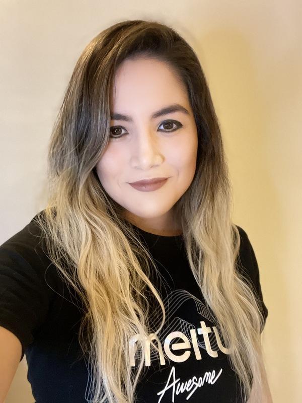 Mulher branca mexicana sorrindo para a câmera com os cabelos soltos