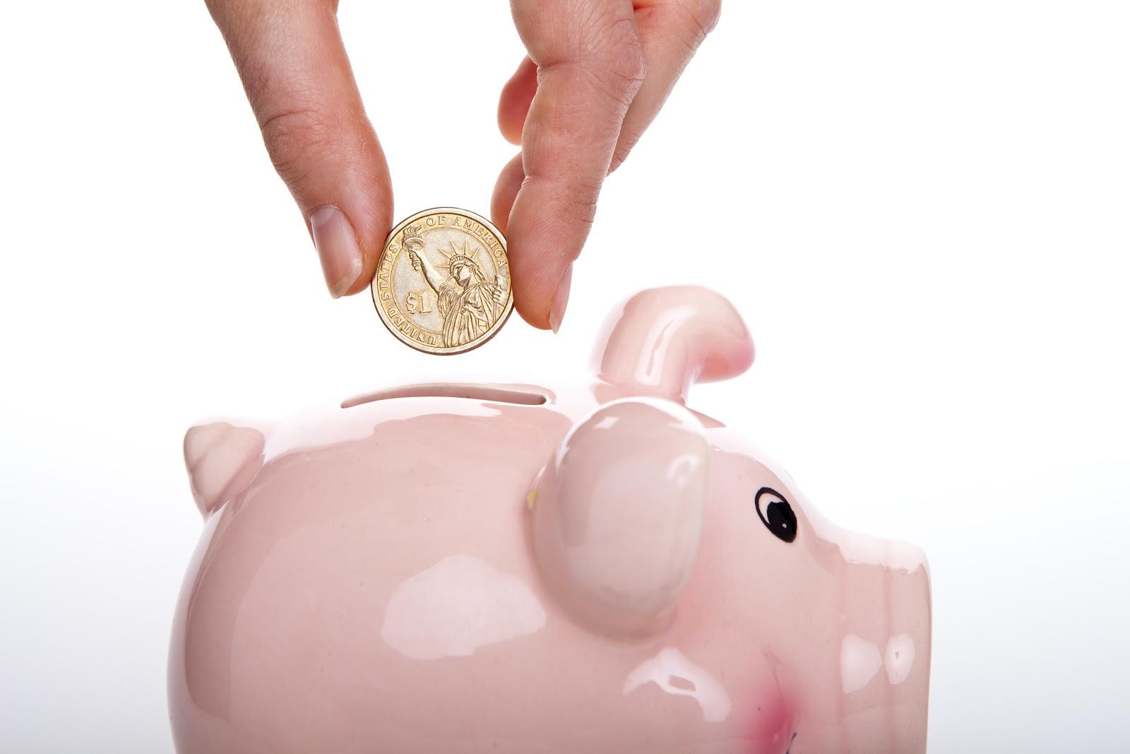 someone putting a coin in a piggy bank