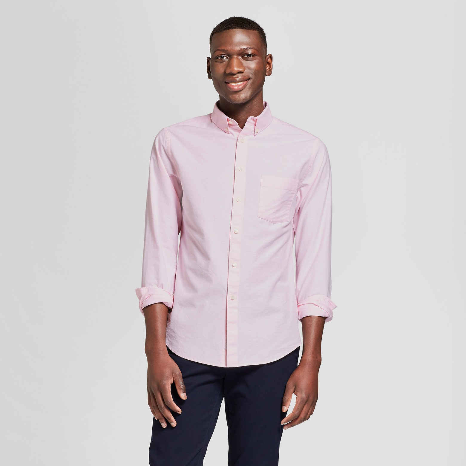 Man wearing a salmon button up with black pants.