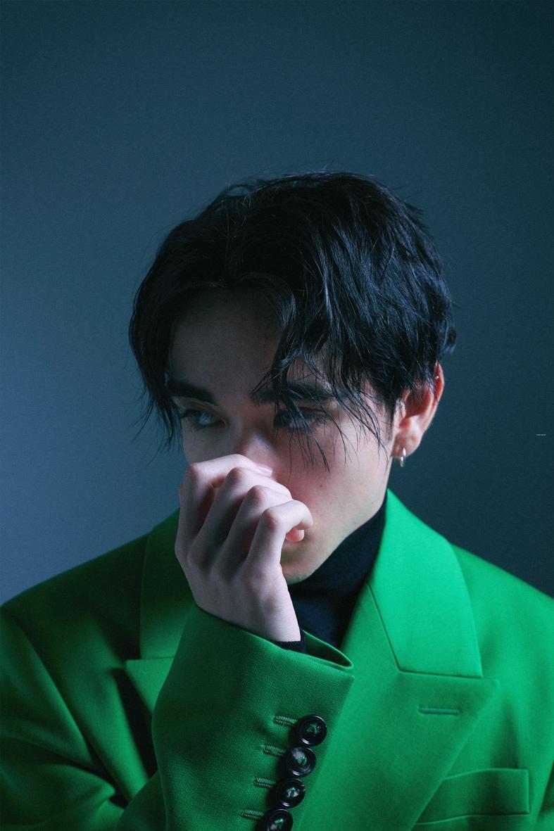 緑のシャツを着た男性中程度の精度で自動的に生成された説明