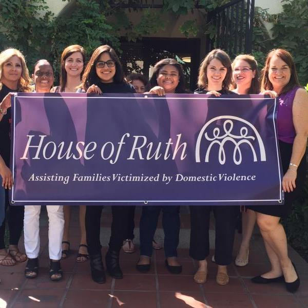 Image of volunteers holding sign that reads: House of Ruth; Assisting families victimized by Domestic Violence