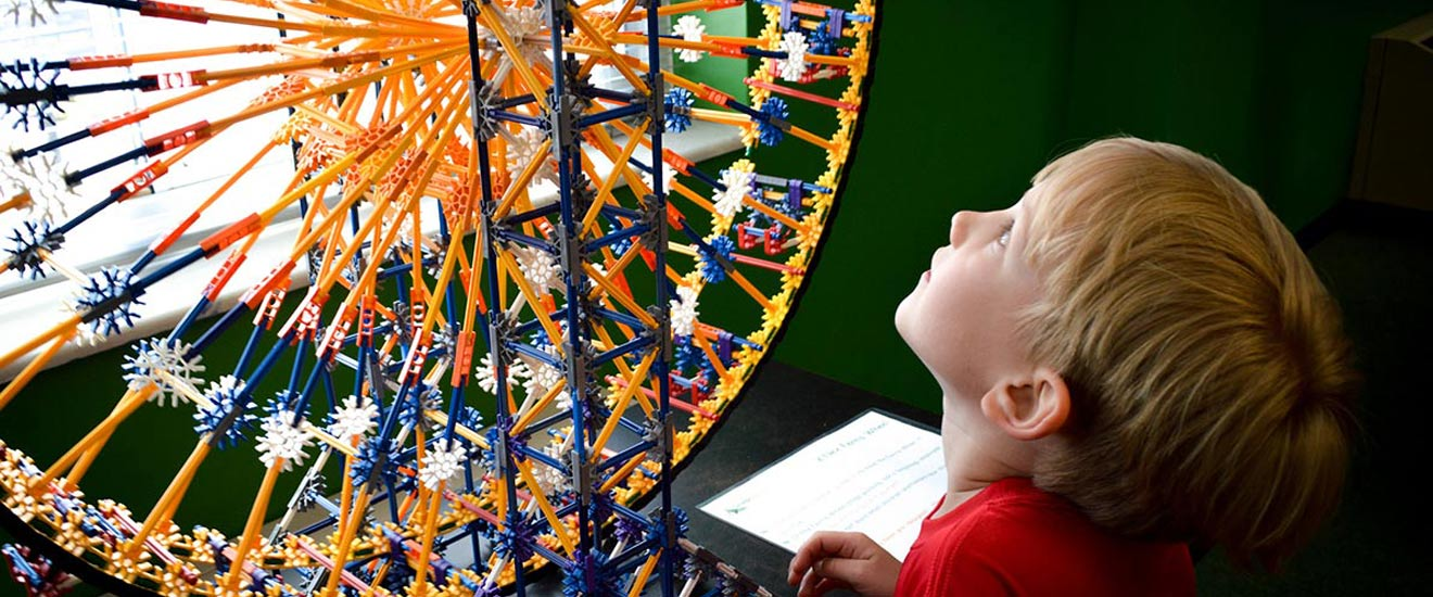 A child gazes in awe up at a ferris wheel made out of kinects.