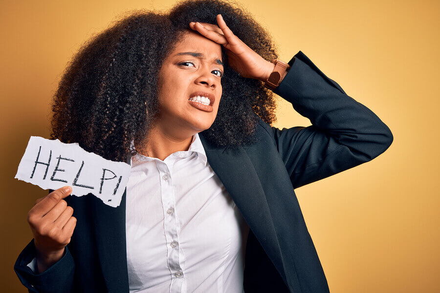 Woman hold up a help sign because she is stressed out and needs stress relief.
