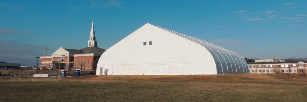A tension fabric building used as a church hall outside a brick spired church in the Midwest