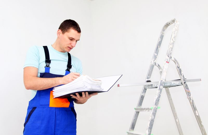 An employee makes notes during a ladder inspection.