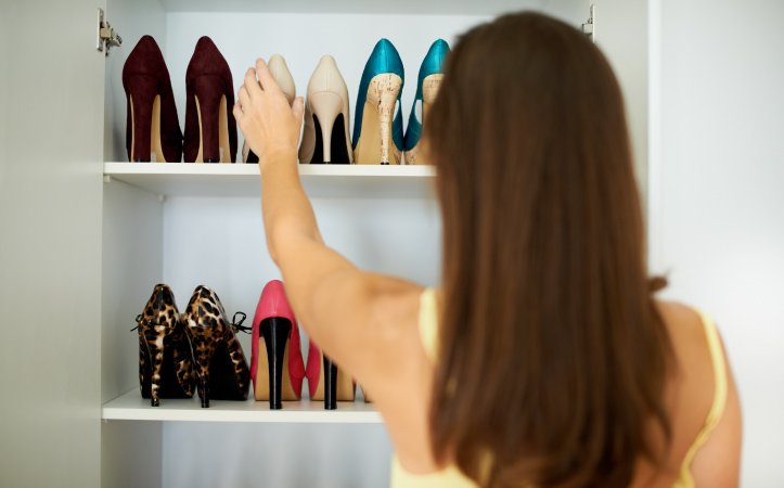 A woman organizing her high heels in her closet rack