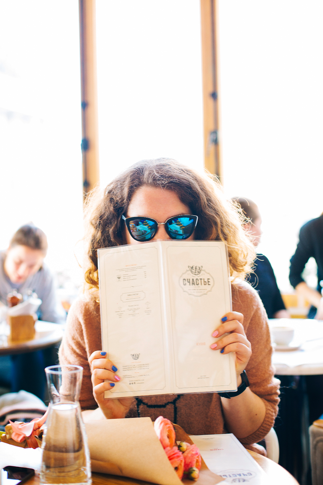 Woman reading a menu at a restaurant.  Selecting food for a healthy living lifestyle.