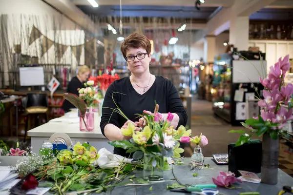Флорист создает цветочную композицию