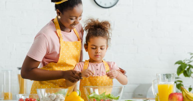 Mãe cozinhando com filha mostrando os benefícios do cogumelo Chaga