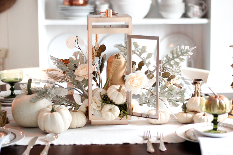 White pumpkin centerpiece with white flowers and an orange gorde on a dining room table.