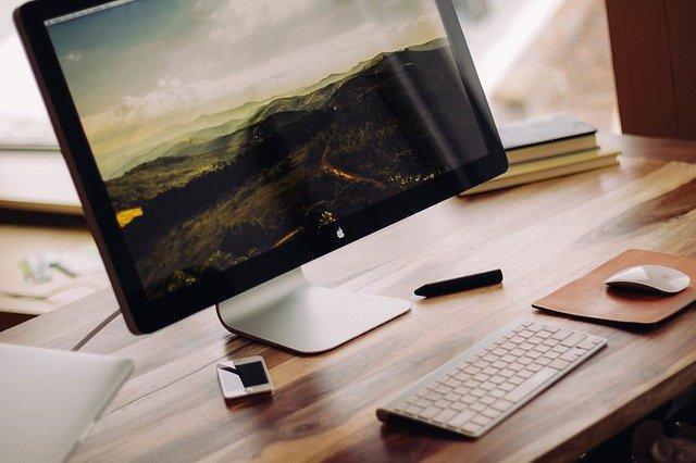 Computador ligado sobre uma mesa de madeiraDescrição gerada automaticamente