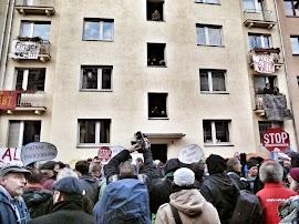 Protestierende vor Wohnhaus mit Transparenten: »Miethaie zu Fischstäbchen«, »Die Stadt gehört uns«, »Finger weg!«, »Alle für Kalle«, »Stop Zwansräumungen«.