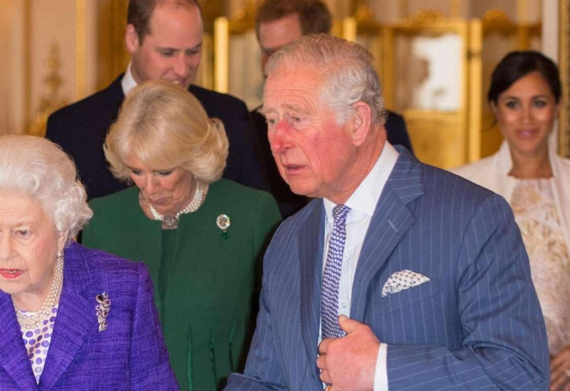 группа людей, стоящих рядом с человеком: герцогиня Корнуолл носит изумрудно-бриллиантовую брошь Prince of Wales Feathers - Getty Images