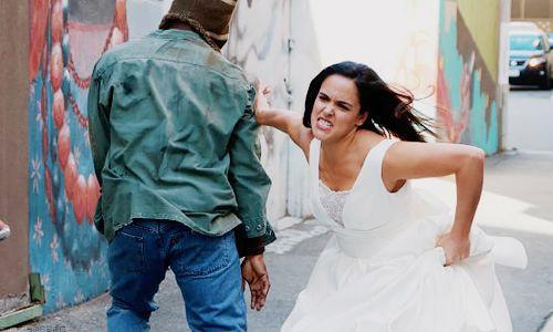 Amy apprehending a perp in her wedding dress