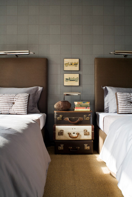 A Stack Of Vintage Suitcases Between Beds