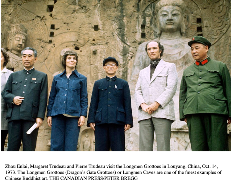 A group of people standing in front of a stone wall  Description automatically generated with medium confidence