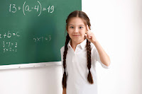 A child standing in front of a blackboard with algebraic variables written on it
