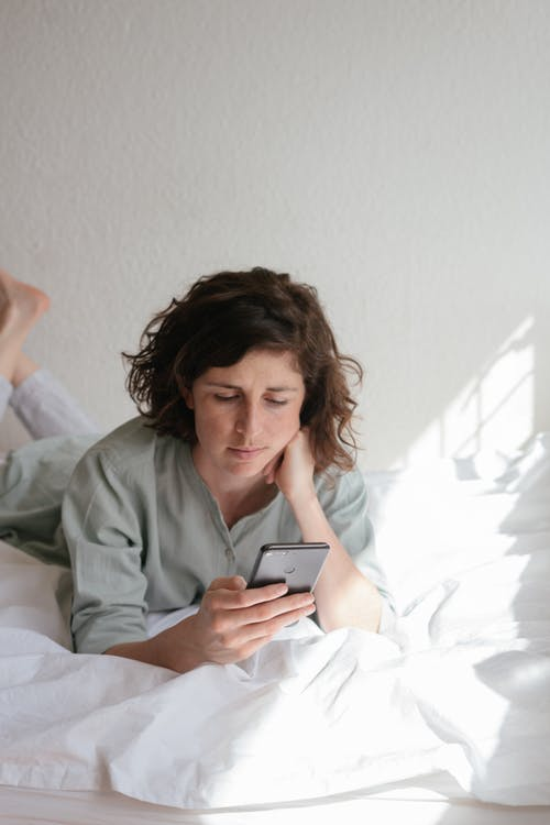Woman Holding Smartphone While Lying In Bed