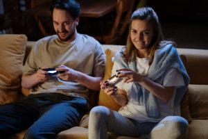 Couple playing video games on a couch
