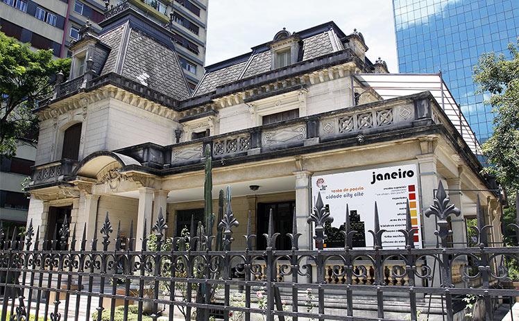 Vista lateral do Museu em SP Casa das Rosas, o qual apresenta, em sua fachada, um banner.