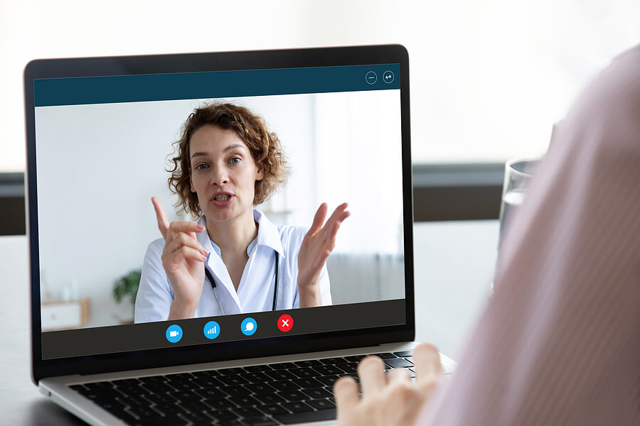 An image of a female online therapist in a lab coat on a laptop screen. Woman with curly hair, talking giving online therapy.