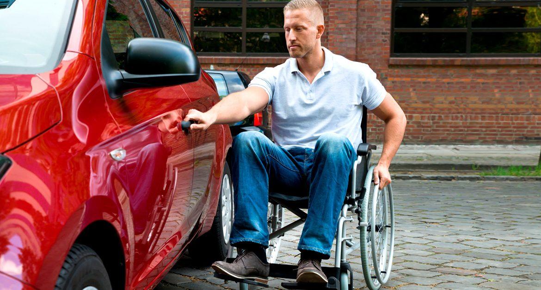 Tetraplégico abrindo a porta de seu carro, que se encaixa no modelo de carros adaptados para deficientes.