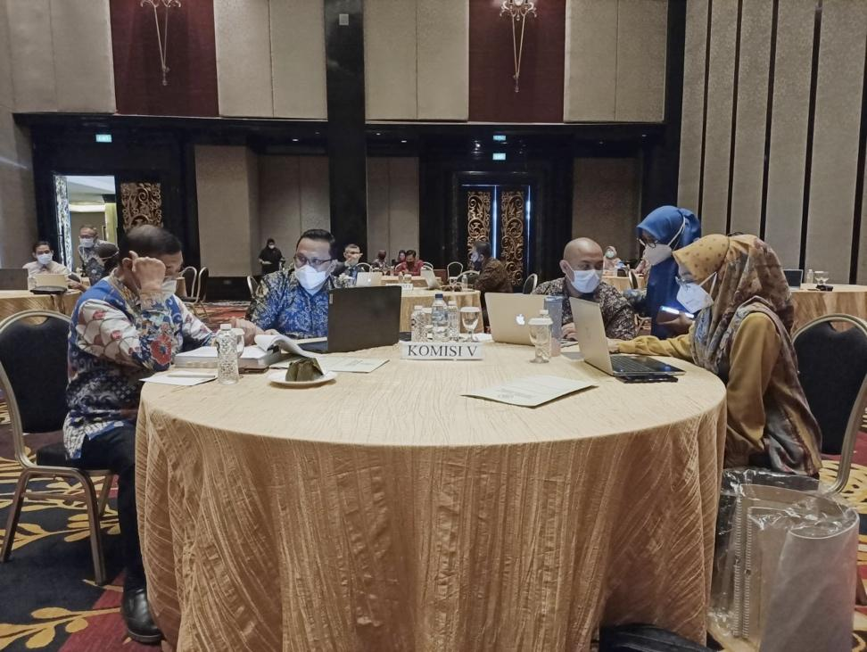 A group of people sitting at a table with laptopsDescription automatically generated with medium confidence