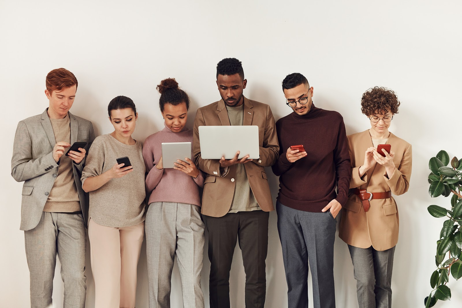 6 people leaning against a way, each of them on technological devices ranging from iPhones and laptops