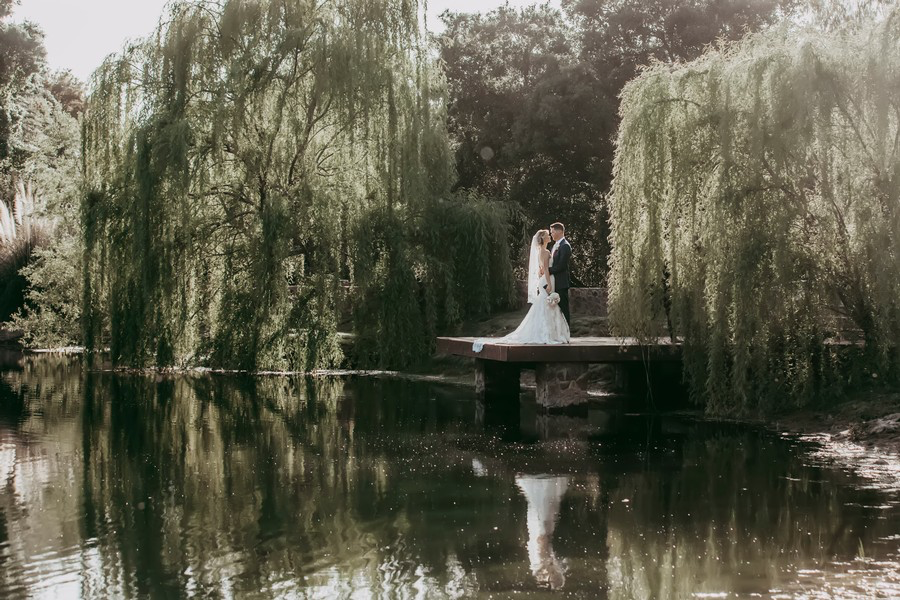 wedding couple at dock on a pond