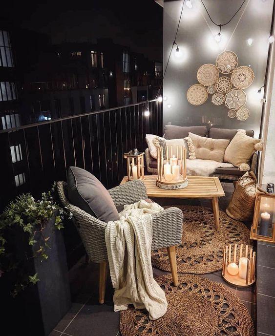 Varanda pequena bem decorada com sofás e poltronas cinza, mesa de centro de madeira, tapetes de palha proporcionando um ambiente rústico, decoração com velas e varal de lâmpadas.