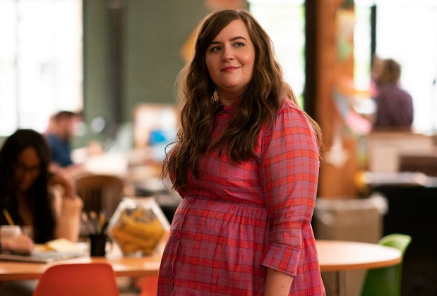 Annie in Shrill. Image: Annie stands center-frame in a pink and purple plaid dress that buttons. I tis high collared, and long sleeved. She stands in the office at the thorn, looking off screen, to the right. Her hair is brown, and hangs loose over her shoulders.