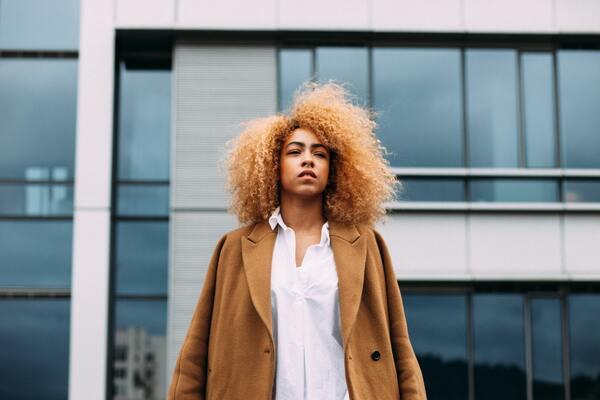 Mulher negra com cabelos soltos posando para a câmera na frente de um prédio espelhado
