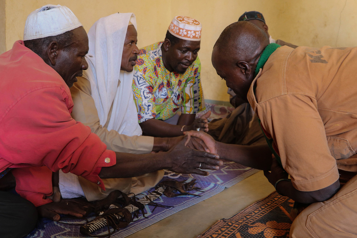Image of Koglweogo members praying together and clasping hands in Burkina Faso's Center-East region