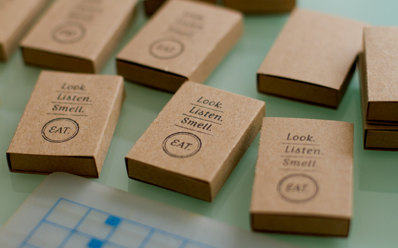 Look listen smell eat business cards they are matchbox style containers made from kraft paper stamped with the logotype when you pull the red tab to read the contact info youll also find a colourmoves