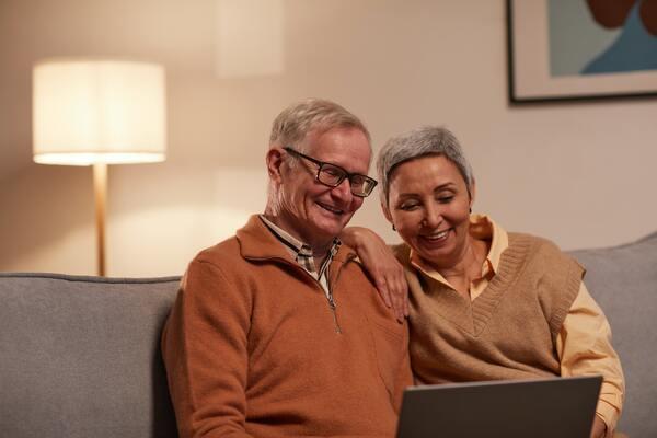 Avós sentados no sofá, rindo e olhando para o notebook