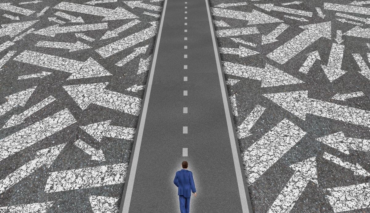 A man in a jacket walking on a road.