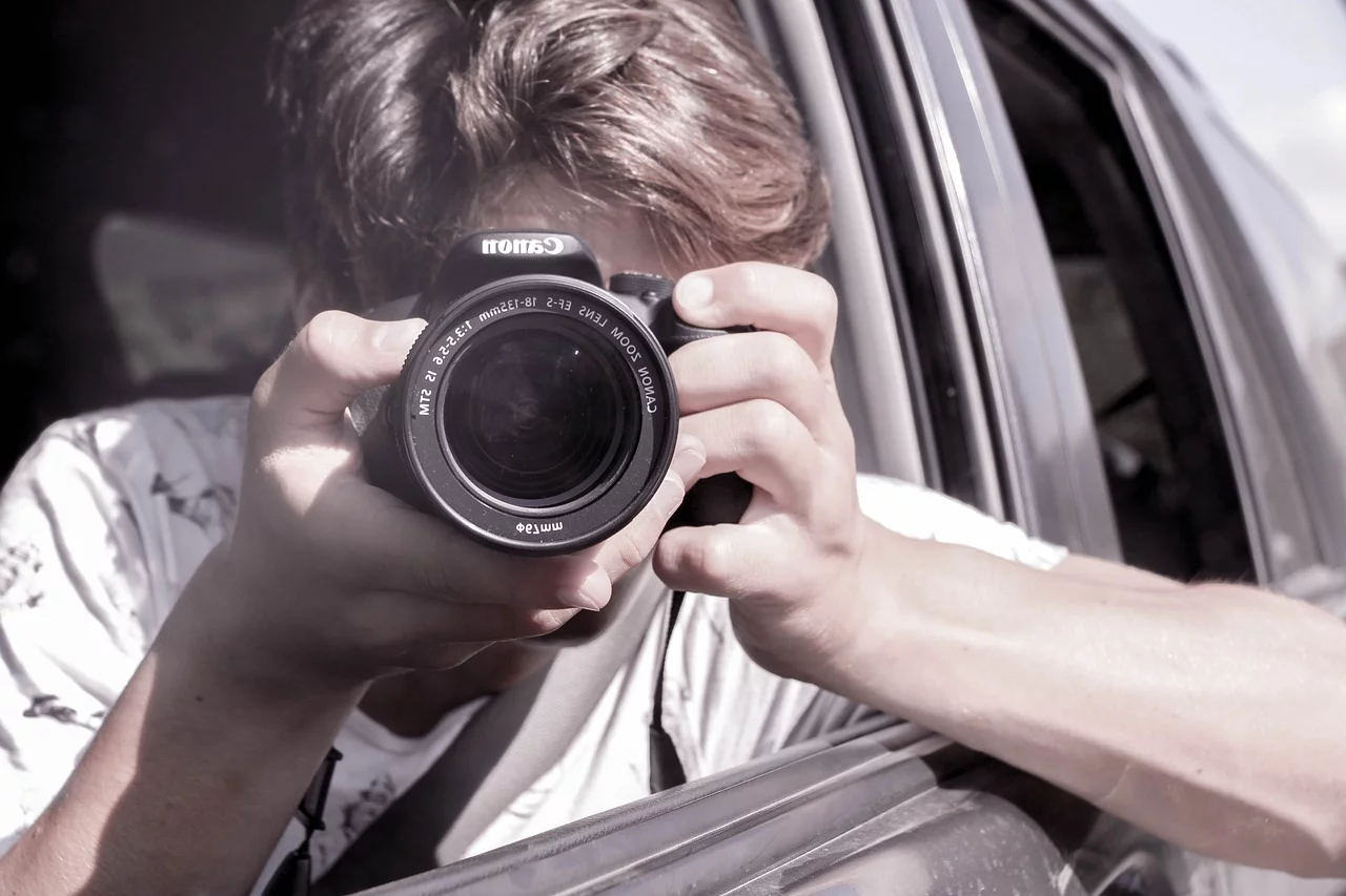 man holding camera outside car window
