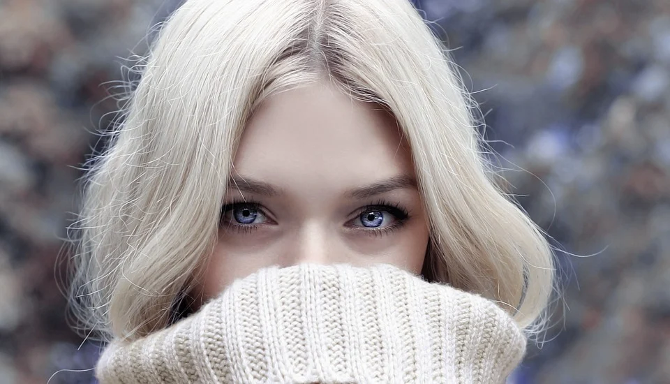woman showing eyes behind sweater