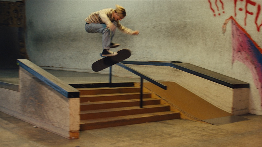 Film still showcasing a part of a private indoor skate park, with stairs, rails and ledges. Slightly off center is Michael captured, wearing a shirt, jeans and black Converse All-Star, as he's in the middle of a flip trick off the stairs with his board - griptape facing the camera - underneath him.
