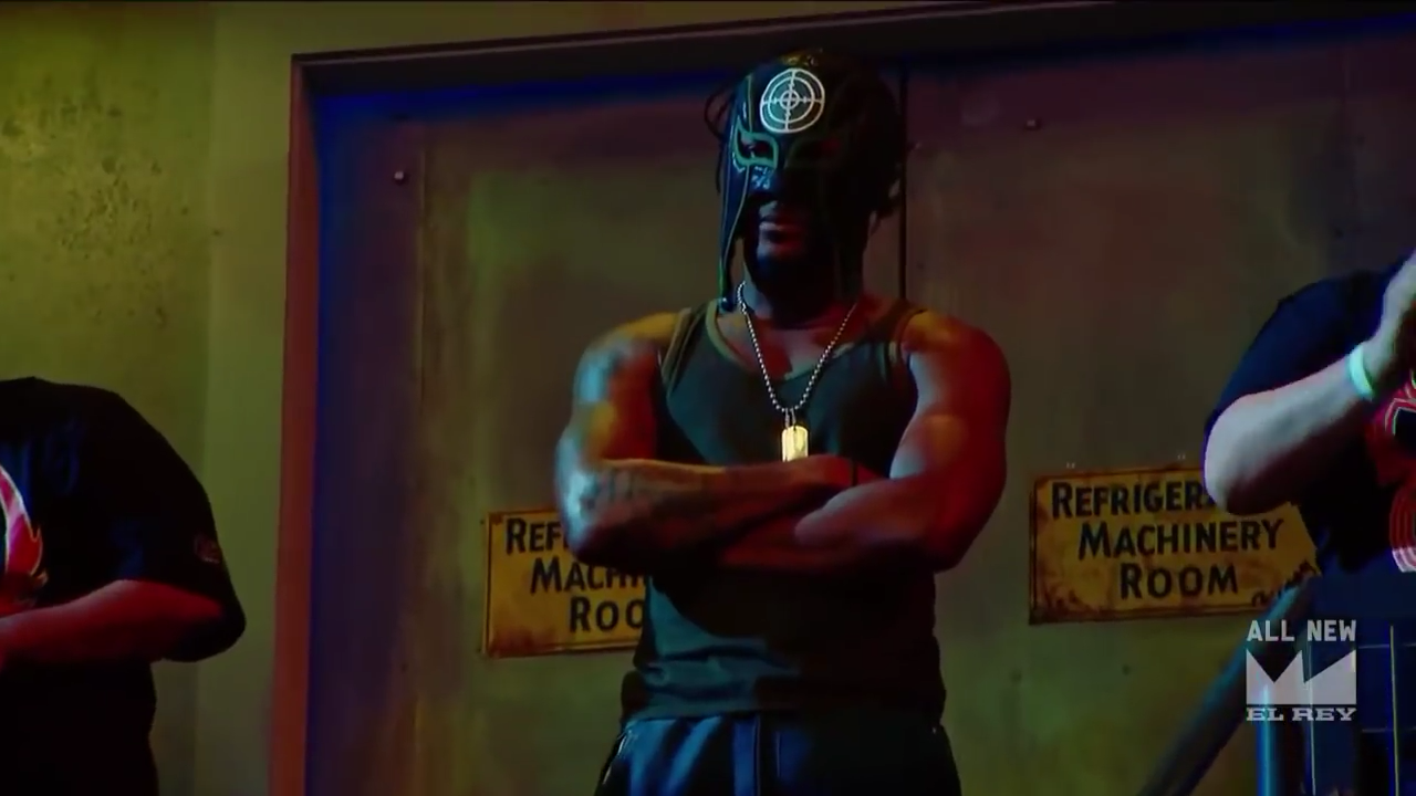 Screen cap from Lucha Underground. Killshot, a black man wearing a mask with a bull's eye on the forehead, stands against an industrial wall surrounded by fans. His arms are crossed and he does not look impressed with the action.