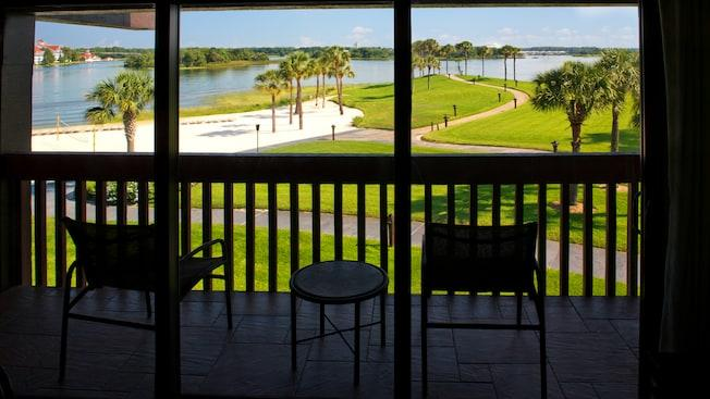 A balcony with lawn furniture and, beyond, Seven Seas Lagoon and Magic Kingdom park
