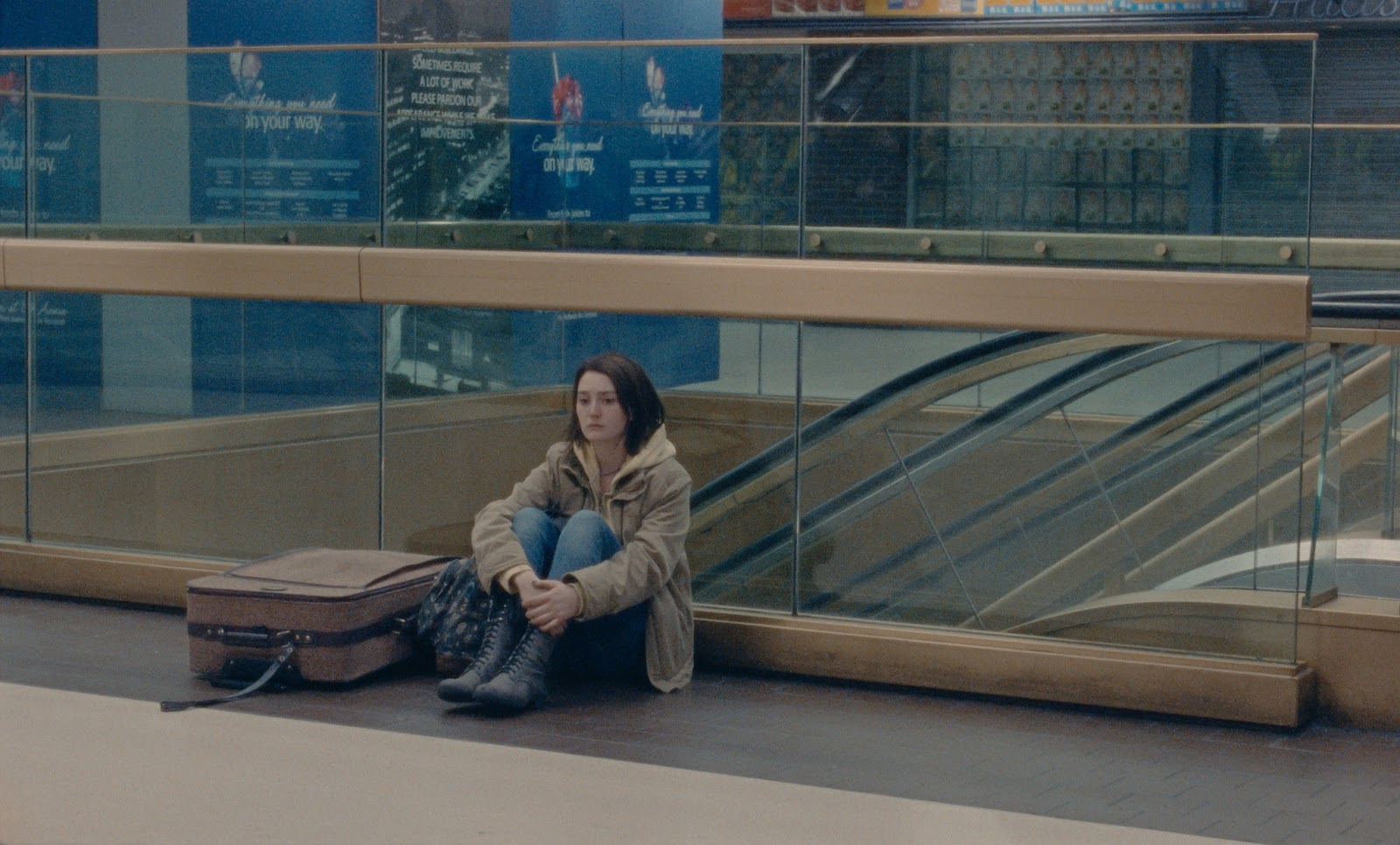 A distraught Autumn sits alone in a bus terminal next to her luggage.