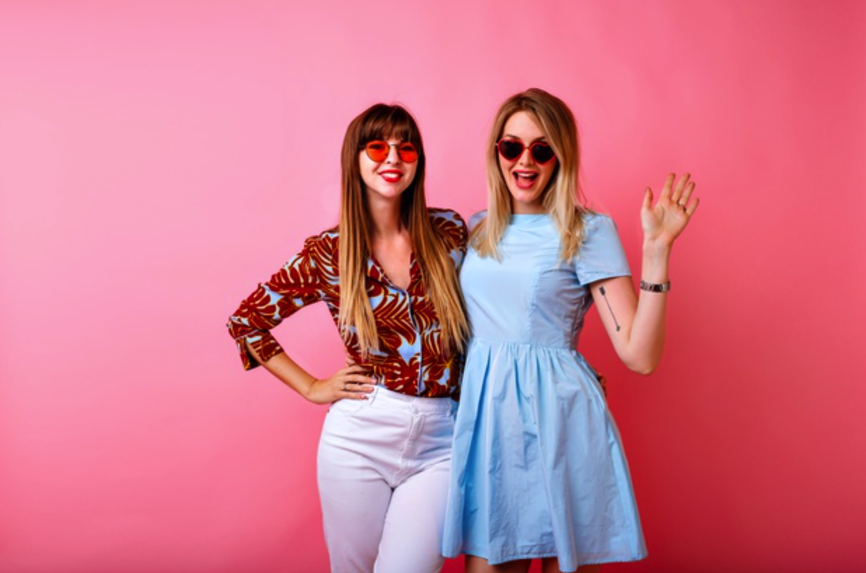 Two happy influencers posing with a pink background | Shopify Merchants
