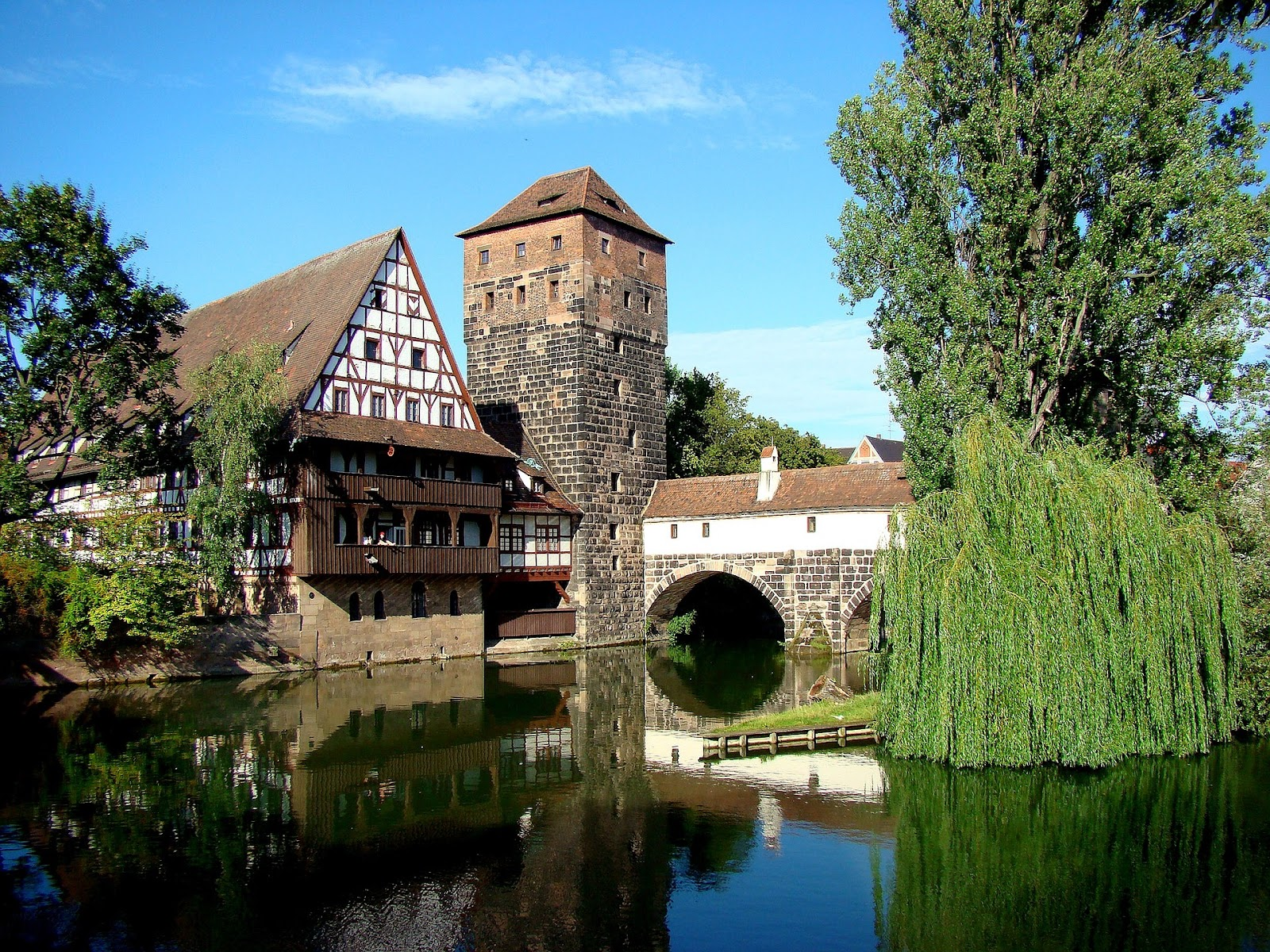 nuremberg medieval weinstadel structure next to river and green trees on a hot sunny day in germany