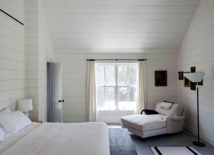 In this bedroom, designer Tiina Laakonen ran horizontal shiplap right up the walls and ceiling. The effect is a seamless transition from wall to ceiling that emphasizes the height and the width of the room. Note also that the curtains are pushed to the side to frame the view.Photograph by Matthew Williams fromRemodelista: A Manual for the Considered Home.