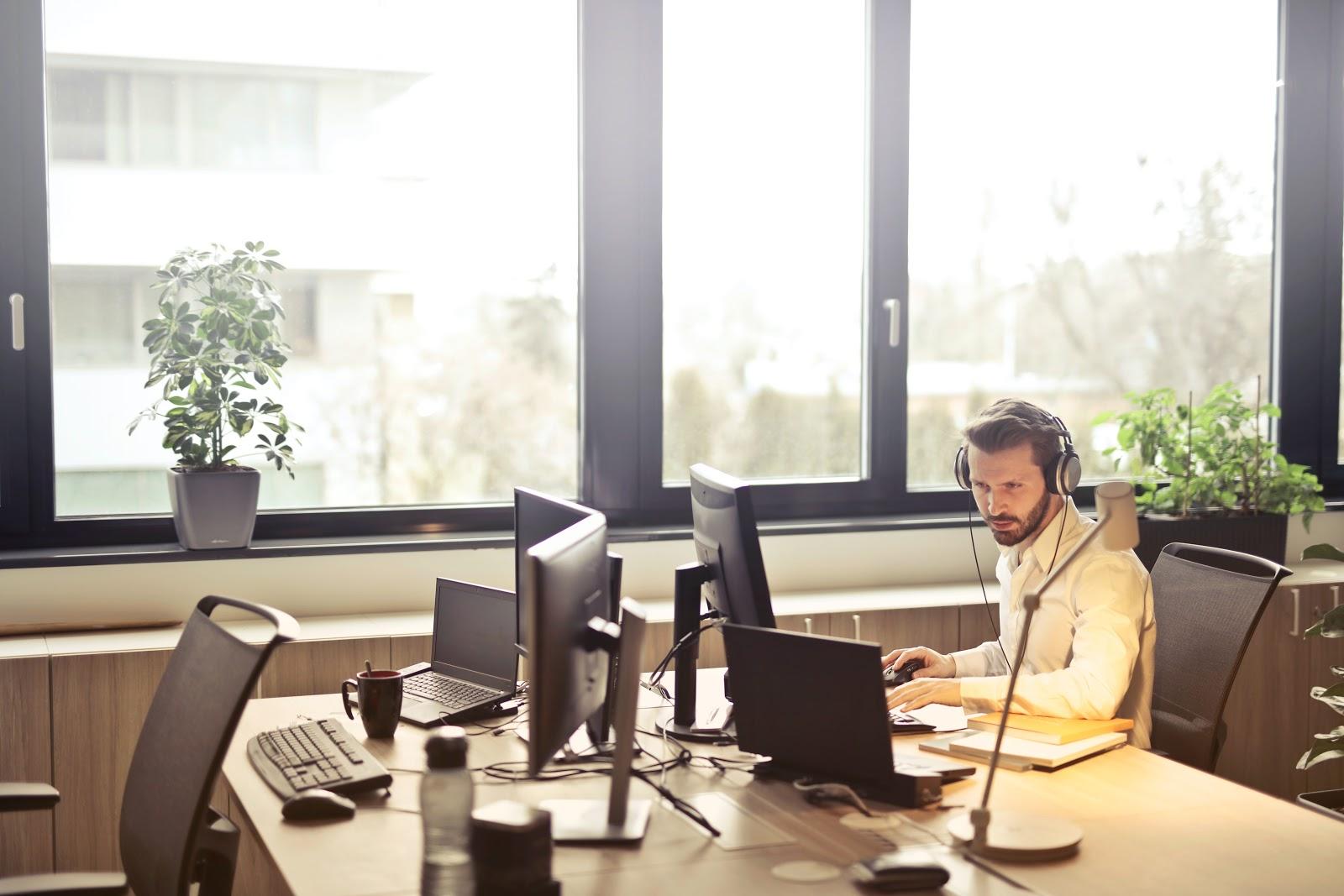 A man with headphones facing computer monitor.