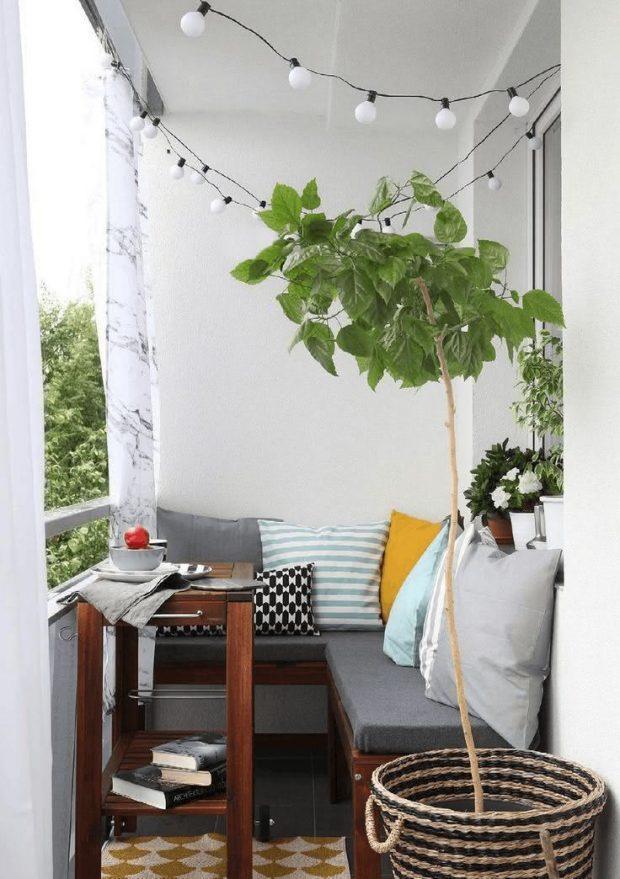 Varanda com paredes brancas, piso cinza, banco de madeira com estofado cinza e almofadas coloridas, mesinha de madeira, vasos de plantas decorando o ambiente e varal de lâmpadas,
